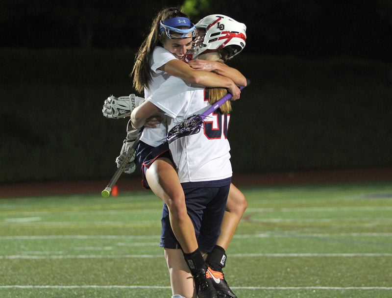 REVIEW PHOTO: MILES VANCE - Lake Oswego senior captains Lauren Gilbert (left) and Riley Hertford closed their careers on a high note, beating Oregon Episcopal School 13-3 to win the Oregon Girls Lacrosse Association state championship in May.
