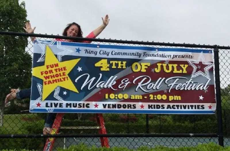 COURTESY OF JAIMIE FENDER - Jaimie Fender, founder and president of the King City Community Foundation that is planning the city's Fourth of July celebration, celebrates putting up a sign promoting the event.
