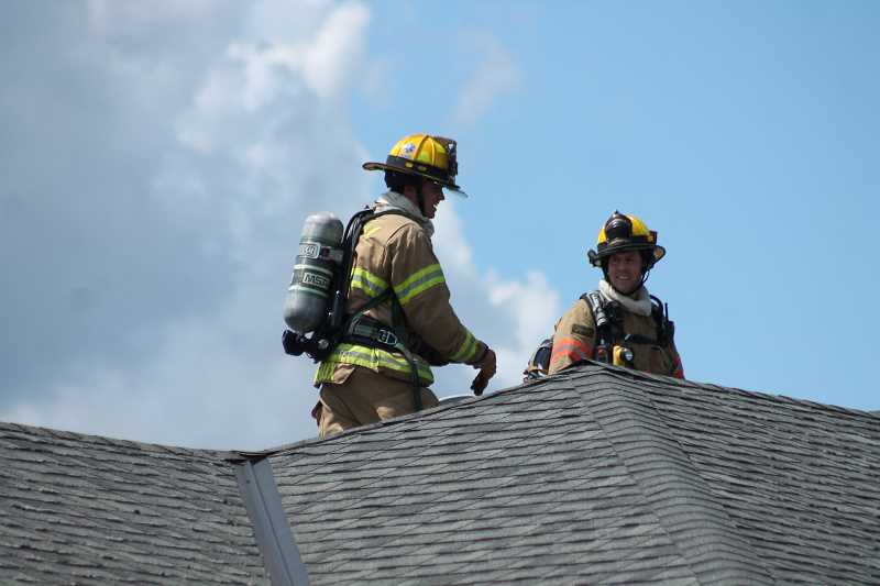 PIONEER PHOTO: CONNER WILLIAMS - Firefighters from the Molalla Fire District make their way onto the roof of Evergreen Court Residential Care Facility to access the vent shafts after learning of smoke in the facility's attic on June 20, 2017.