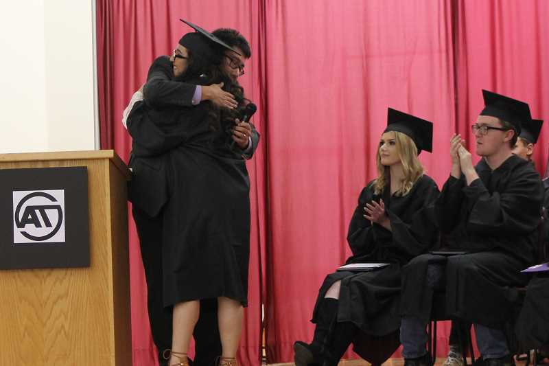 SPOKESMAN PHOTO: ANDREW KILSTROM - Art Tech science teacher Will Lee gives graduate Sarah Sandoval a hug before she receives her diploma.