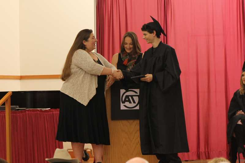 SPOKESMAN PHOTO: ANDREW KILSTROM - Brandon Vahdat gets a congratulations from Principal Saskia Dresler after receiving his degree Tuesday, June 13.