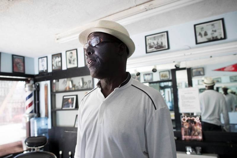 PORTLAND TRIBUNE: JAIME VALDEZ - Rickey Brame surrounded by framed photos of neighborhood residents who used to visit the barber shop started by his father at Studio Six Nine Hair Design. It was named after the year he graduated from Jefferson High School.