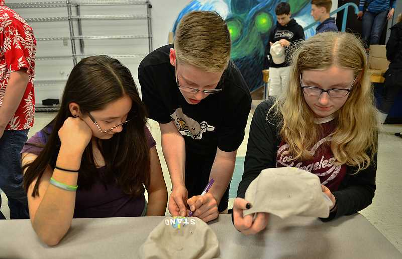 REVIEW PHOTO: VERN UYETAKE - Lakeridge Junior High finishers (from left) Nicole Taniguchi, Ben Connolly and Talia Dalton share a moment at the eighth-grade celebration on June 12.