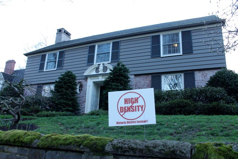 TRIBUNE PHOTO: LYNDSEY HEWITT - Many homes Eastmoreland had signs presenting their opinions for or against the proposed historic district.