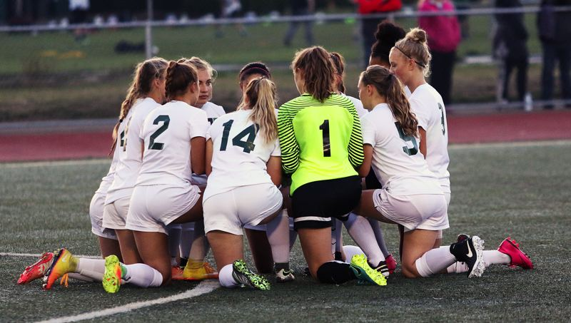 DAN BROOD - Lexie Sawin (1) gathered with her Tigard teammates before a match last fall.