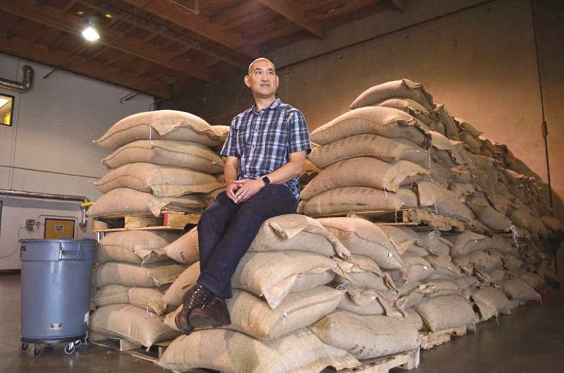 HILLSBORO TRIBUNE PHOTO: JOHN WILLIAM HOWARD - Longbottom Coffee and Tea General Manager Leo Chung sits atop bags of green coffee beans in the Longbottom warehouse in Hillsboro.