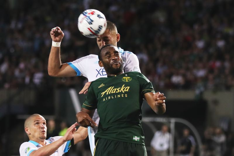 TRIBUNE PHOTO: JAIME VALDEZ - Seattle Sounders midfielder Clint Dempsey heads the ball over the Portland Timbers' Amobi Okugo for the game-tying goal in the second half at Providence Park.