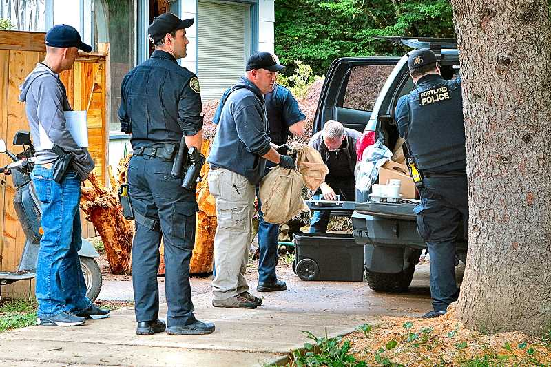 DAVID F. ASHTON - After serving a search warrant, officers load evidence from this Sellwood house into a waiting police vehicle.