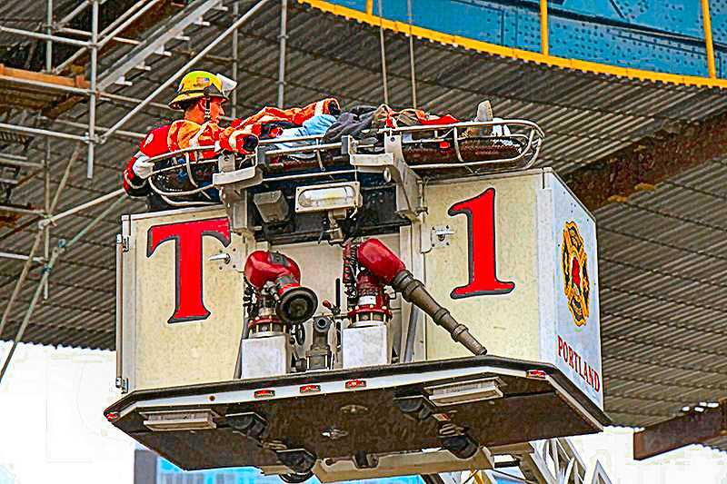 COURTESY OF PORTLAND FIRE & RESCUE  - In the February 8th fall, at the Ross Island Bridge, an injured worker was strapped to a gurney, which was lashed to the aerial platform of PF&R Truck 1 for lowering to a waiting ambulance.