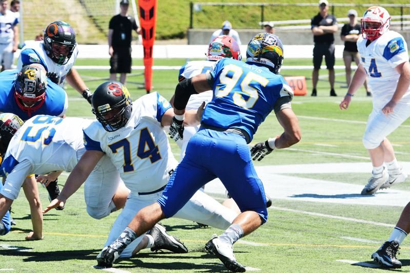 SPOTLIGHT PHOTO: JAKE MCNEAL - North defensive end Boogie Davis of Westview (95) shakes South offensive guard/tackle Colton Albertson of St. Helens (74) in pursuit of South quarterback Ty Hargis of Lebanon as the South won the 70th Les Schwab Bowl 10-7 on Saturday, June 24, at Hillsboro Stadium.