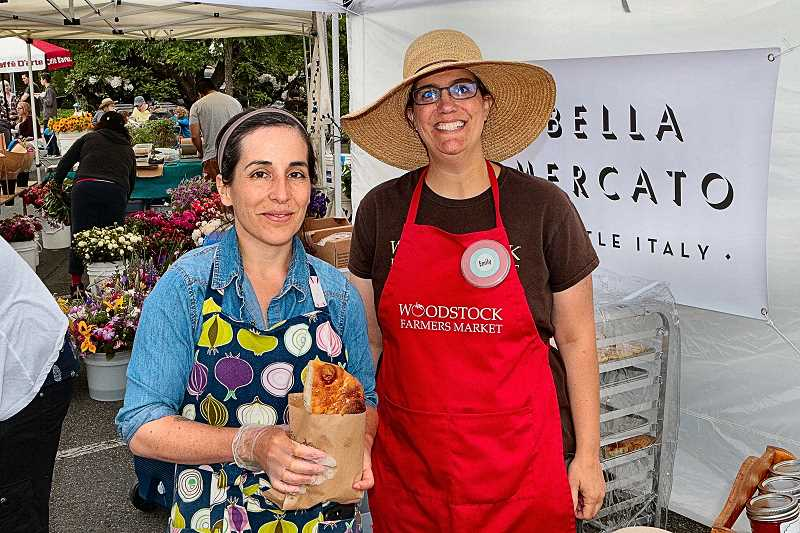 "DAVID F. ASHTON - New bakery owner Michelle Vernier from ""Bella Mercado"" spends a moment with Woodstock Farmers Market Manager Emily Murnen."