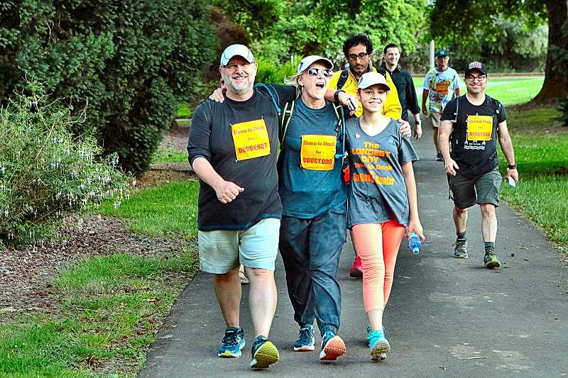 DAVID F. ASHTON - Richard and Tatyana Sundvall walk into Sellwood Park with Arina Zhibar, at the end of their Dawn to Dusk Walk for Dougy. Arina is Tatyanas niece, visiting from Russia, who was orphaned two years ago - part of the reason for the Sundvalls fundraising walk.