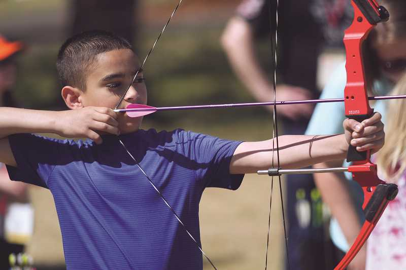 PHIL HAWKINS - Volunteers were on hand to help train campers in archery, using compound practice bows to take aim at a variety of targets at the camp's archery course.