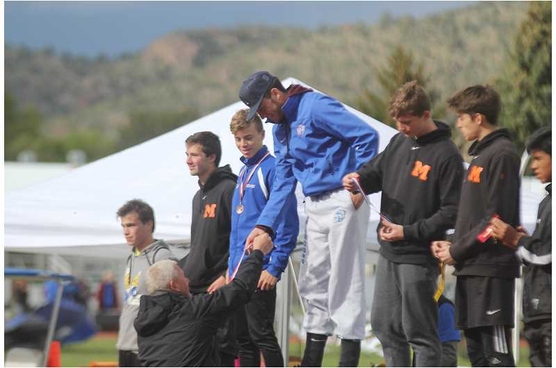 WILL DENNER/MADRAS PIONEER - Darrell Yount, seen here giving Harrison Manu a medal at TVC districts May 13 in Prineville, announced he will no longer be the head track and field coach at Madras. Instead, he will coach track and field at the Warm Springs K-8  Academy, where he is already a physical education teacher.