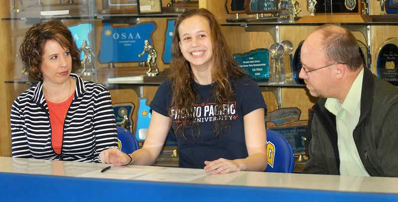 SETH GORDON - Newberg High School water polo standout Katie Kisling signs a letter of intent to play for Fresno Pacific earlier this spring. Kisling is one of nine NHS athletes moving on to compete for an NCAA Division I or II institution.