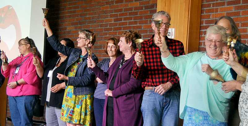 SETH GORDON - Retiring employees of the Newberg School District ring ceremonial bells to mark the end of their final school year earlier this month at the district's annual Crystal Apple Awards ceremony.
