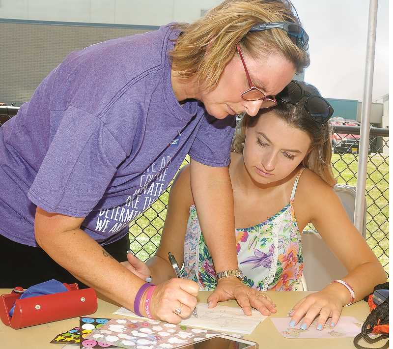 GARY ALLEN - Ann Marie Bennett and daughter Giselle create a luminaria in honor of Chehalem Valley Middle School counselor Susan Clayton, who succumbed to breast cancer.