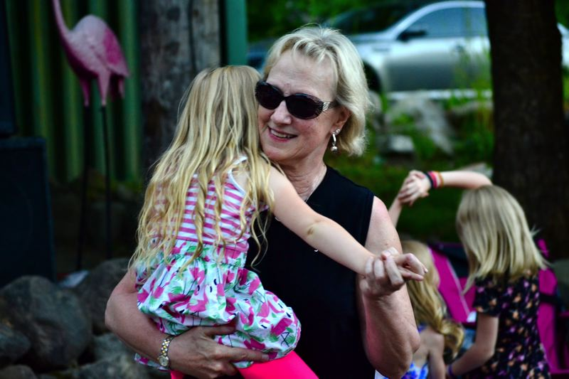 POST PHOTO: BRITTANY ALLEN - Clackamas County Bank President Cathy Proctor-Stuchlik dances to tunes by The Substitutes with her granddaughter at the Party on the Patio event on Saturday, June 24.
