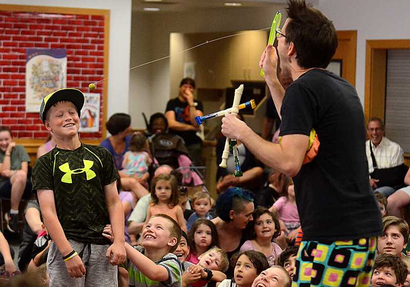 SPOKESMAN PHOTO: VERN UYETAKE - Alex Zerby, the Zaniac,  gets Dallas Michel involved with his act with the paddle ball at the Wilsonville Library June 22.