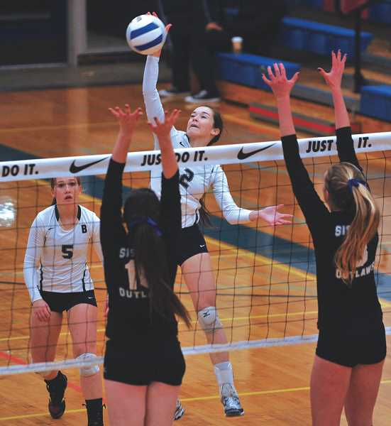 NEWS-TIMES FILE PHOTO - Banks' MaKenna Partain hits between the block of Sisters' Brenna Weems (10) and Hawley Harrer (3) during a state finals match. Banks lost the match but won the state championship a year later.