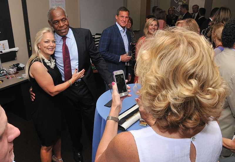 REVIEW PHOTO: VERN UYETAKE - Darcie Terrell gets her picture taken with Danny Glover at Park Academy during An Evening with Danny Glover, a fundraiser held June 22 in Lake Oswego.