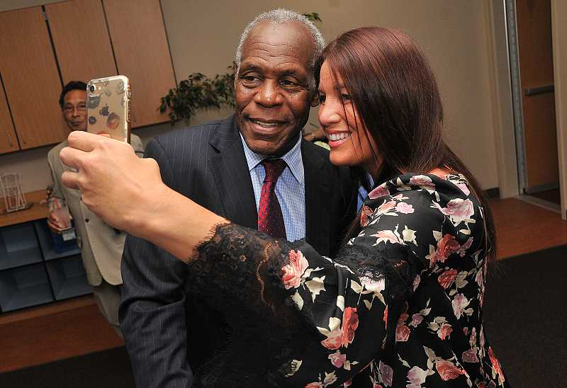REVIEW PHOTO: VERN UYETAKE - Cristina Emmert snaps a photo with actor Danny Glover at fundraiser for Park Academy in Lake Oswego last week.