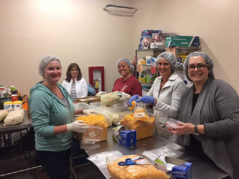 SUBMITTED PHOTOS - Erin Lile (from left), Carol Hughes, Tam Hixson, Mo Colburn and Barbara Mount packed bulk foods into individual portions at Tualatin School House Food Pantry during Windermere Real Estates day of service on June 9.
