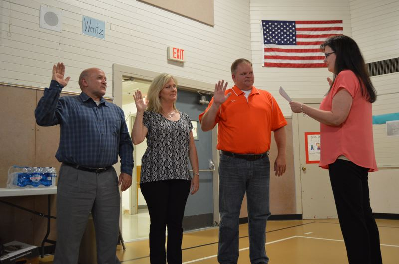 SPOTLIGHT PHOTO: NICOLE THILL - Pictured from left to right: School board secretary and executive assistant Julie Hinkle swears in Tim Brooks, Lisa Maloney and Phil Lager to serve on the Scappoose School Board during a work session Monday, June 26.