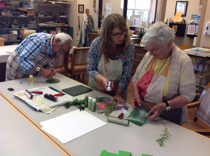 SUBMITTED PHOTO - Willamette View art therapist Kristen Larsen, center, shows residents Dan and Nilda Rego how to make monoprints using the Gelli printing process. Dan Rego and Larsen's work will be on display at the Alzheimer's art exhibit on July 7.
