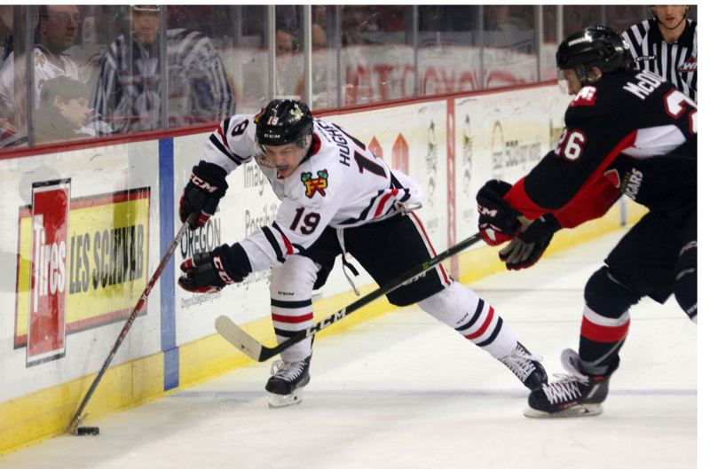 TRIBUNE FILE PHOTO: JONATHAN HOUSE - Ryan Hughes (left) of the Portland Winterhawks gets to the puck before a Prince George opponent during a game last season.