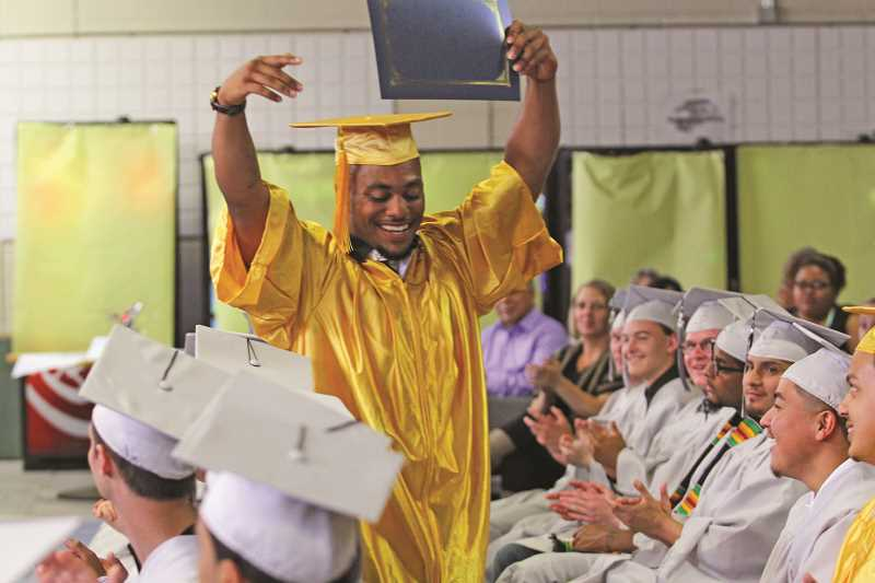 INDEPENDENT PHOTO: JULIA COMNES - Kayshawn shows off his GED certificate at the June 30 graduation for MacLaren and Hillcrest youth correctional facilities.