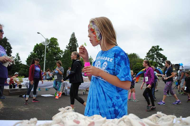 NEWS-TIMES PHOTOS: EMILY GOODYKOONTZ - Addy Lawson blows bubbles by the table full of love rocks as 5K runners finish the race behind her.