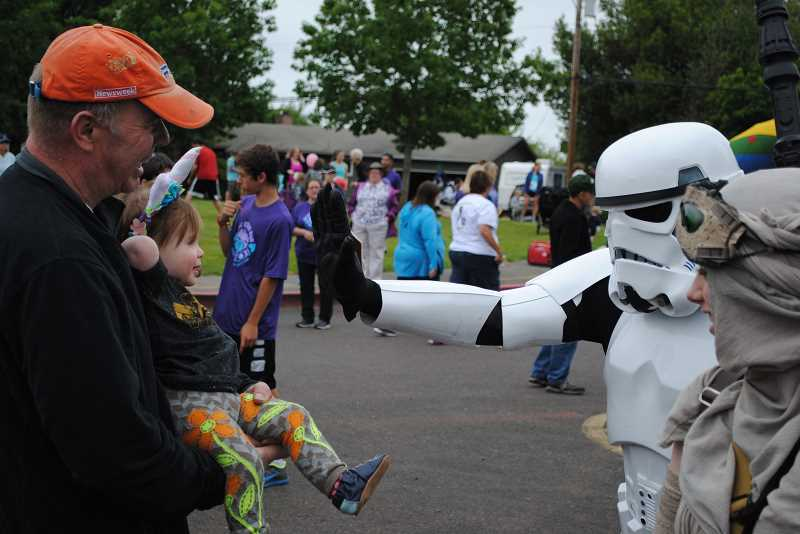 NEWS-TIMES PHOTOS: EMILY GOODYKOONTZ - Bill Huff holds his daughter Heidi as she receives a high five from Star Wars storm trooper Luke Killam/character Rey.