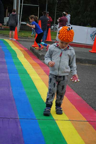 NEWS-TIMES PHOTOS: EMILY GOODYKOONTZ - 005: Miles Besse was fascinated with the giant rainbow stripe on the road and the bubbles floating in the air near the finish line.