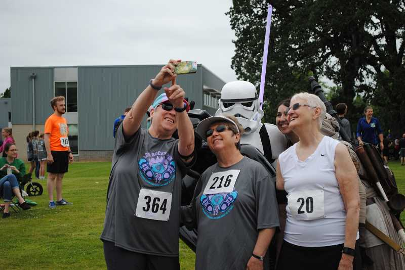NEWS-TIMES PHOTOS: EMILY GOODYKOONTZ - 007: A group of older runners poses for a selfie with a Star Wars Storm Trooper. 008: A dad pins a runner number on his daughter.
