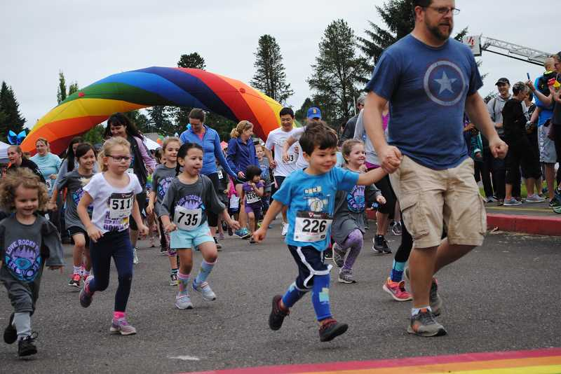 NEWS-TIMES PHOTOS: EMILY GOODYKOONTZ - Kids ages 7 and under and their parents run during the second heat of the kid's fun run at the 2017 Love Rocks Run on July 1.