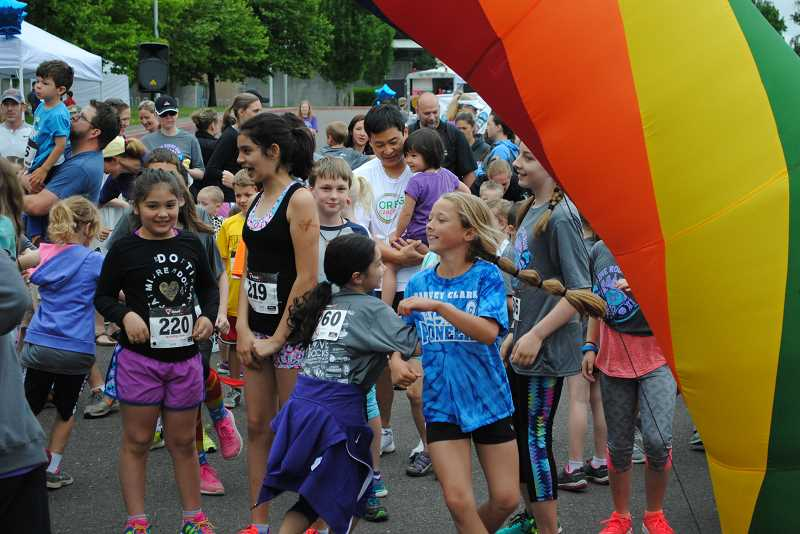 NEWS-TIMES PHOTOS: EMILY GOODYKOONTZ - Addy Lawson twirls and skips with her friend as the kids warm up before the fun run.