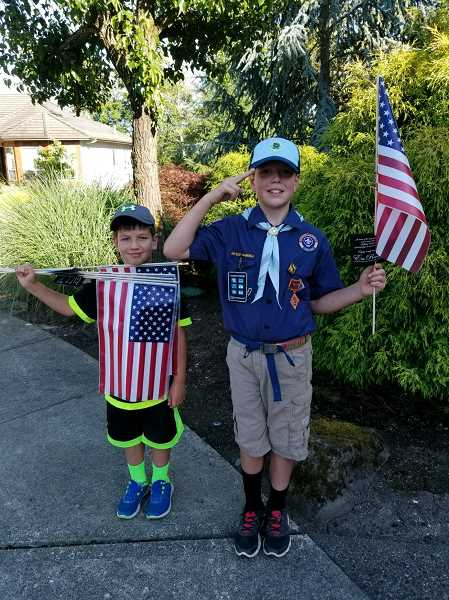 SUBMITTED PHOTO - Cub Scouts Evan and Noah Robledo take a picture with flags Thursday, June 29.