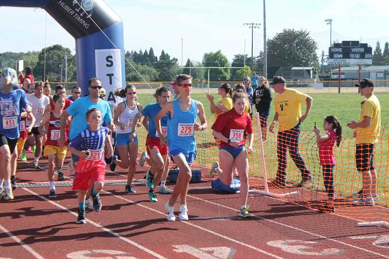 PIONEER PHOTO: CONNER WILLIAMS  - Marcus David, 15,of Lake Oswego (275) and Batya Beard, 18, of Portland (358) were the first to cross the finish line for the men and women during the sixth annual Freedom 5K race.