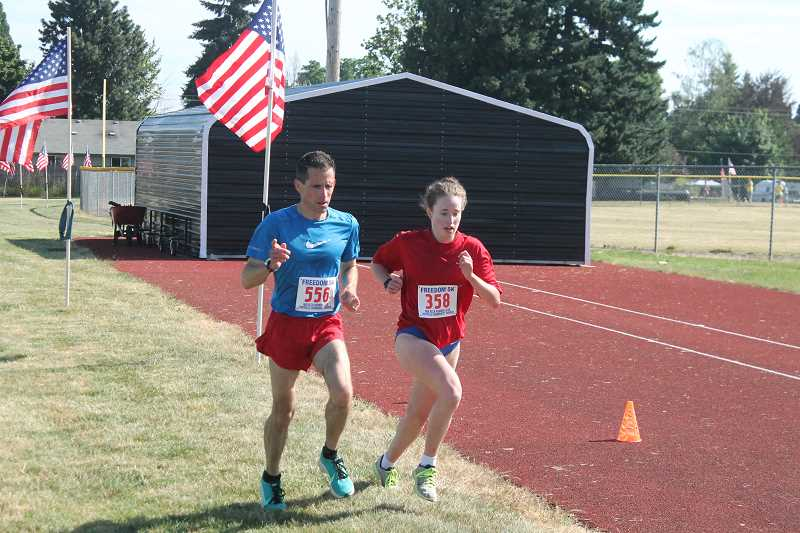 PIONEER PHOTO: CONNER WILLIAMS  - Batya Beard (358) and her father, Peter, 51(556) finish the sixth annual Freedom 5K race together with about 100 meters left. Peter was one second behind his daughter and finished first in his age group.