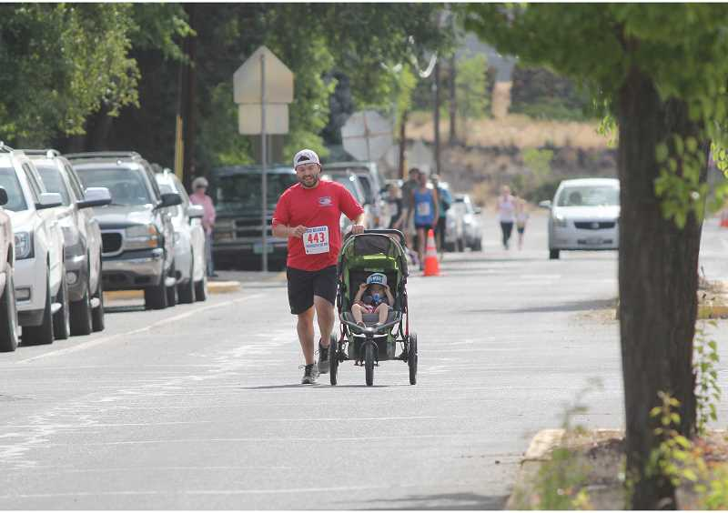 WILL DENNER/MADRAS PIONEER - Jordan Beamer, Bud's son and Todd's brother, and his two-year-old daughter, Grace Ann, finish the two-mile fun run.