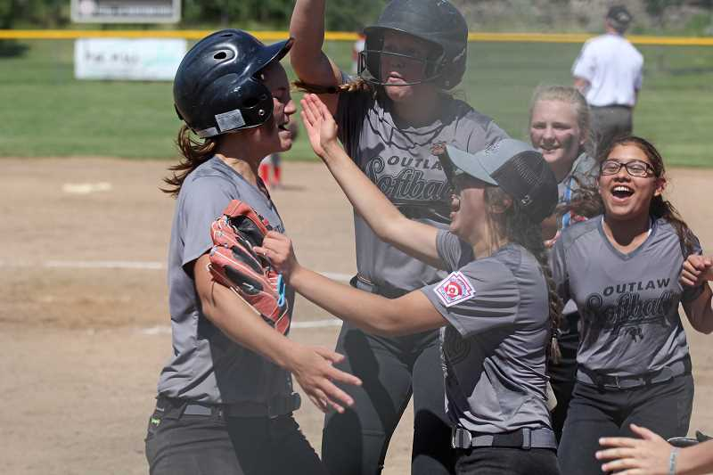 WILL DENNER/MADRAS PIONEER - Jefferson County Little League softball players Hannah Holliday, Natalie Lockey and Shanti Rodriguez embrace Liz Barker (left) at home plate after Barker blasted a two-run home run Saturday against Redmond. The juniors softball team, which lost 15-5 in the championship to Warm Springs Nation, is made up of players from Sisters, Prineville and four from Madras: Holliday, Lockey, Rodriguez and Fiona White.