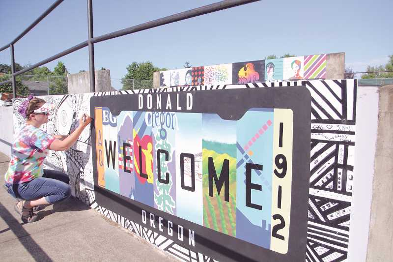 LINDSAY KEEFER - Sara Bailey, adviser of North Marion Art Honor Society, puts some finishing touches on the latest mural at Donald Skate Park, which uses a Zentangle to tie in the new piece with last year's mural (in the background).