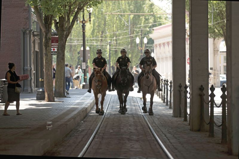 TRIBUNE PHOTO: JAIME VALDEZ - Former members of the Portland Police Bureaus Mounted Patrol Unit rode along the light rail tracks towards the Northwest District last Friday. From left they were: Officer Melissa Newhard on Monte, a Belgium quarter horse; Officer Cassandra Wells on Asher, a Percheron, and Sergeant Marty Schell on Major, an Appaloosa-Percheron.