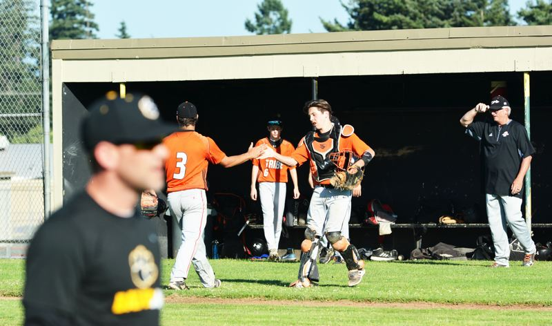 SPOTLIGHT PHOTO: JAKE MCNEAL - Thomas Cook of Banks high-fives Tyler Souvenir as he retires St. Helens with a strikeout.