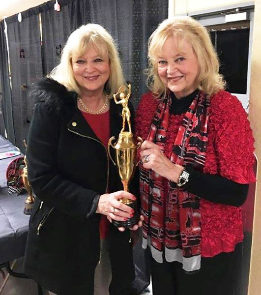 CONTRIBUTED PHOTO - Twin sisters Suzanne Strain-Lackman and Diana Strain-McClelland pose with the state championship trophy from their 1958 season at David Douglas.