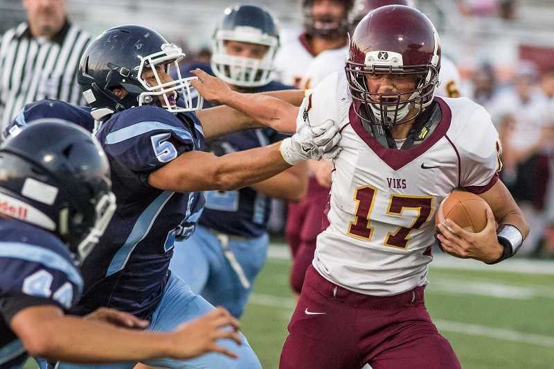NEWS-TIMES FILE PHOTO: CHASE ALLGOOD - Forest Grove quarterback Lukas Janac takes on a tackler during a game versus Hillsboro's Liberty High School early in the 2016 season.