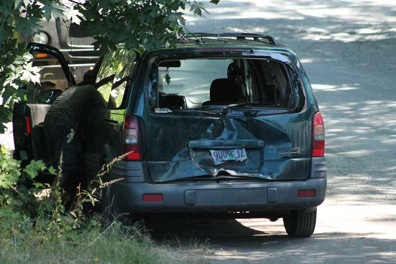 PIONEER PHOTO: CONNER WILLIAMS - The rear of a green Pontiac van can be seen caved in after fire officials say it was rear-ended by a semi-truck as the van was turning into the Wagon Wehll Park entrance from southbound Highway 213.