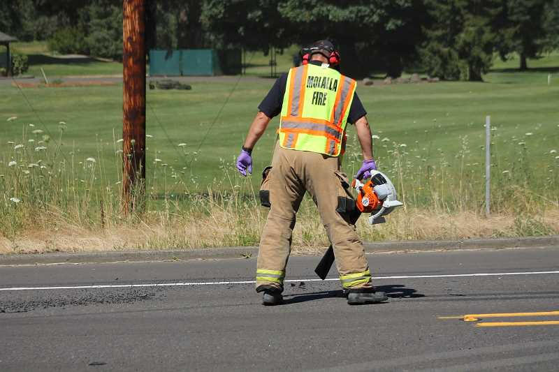 PIONEER PHOTO: CONNER WILLIAMS - An official from the Molalla Fire District cleans up glass and debris shards from the roadway.