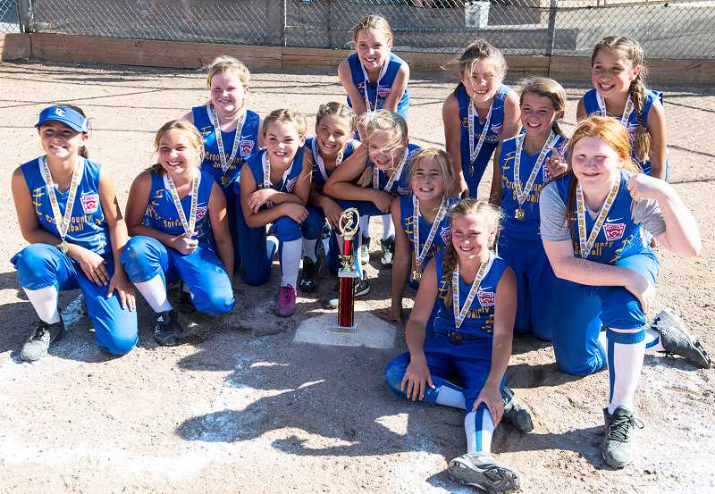 LON AUSTIN/CENTRAL OREGONIAN - Members of the Crook County minors softball all-star team pose with their first place trophy from the District 5 regional tournament. The district win qualified the Cowgirl team for the state tournament, which will start next Friday.